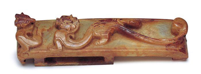 漢代.雙龍紋玉劍璏 ; 劍璏表面高浮雕雙龍紋,以一大一小、或屈或伸的姿態營造戲劇性的張力。(圖二)