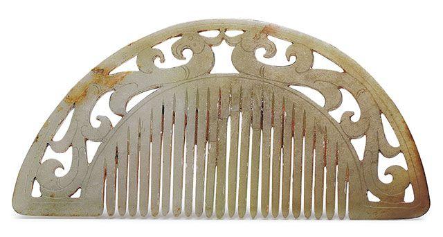 漢代.雙鳳紋玉篦:梳齒上方透雕一對鳳鳥,以反向對稱的型態構成相背式的組合。