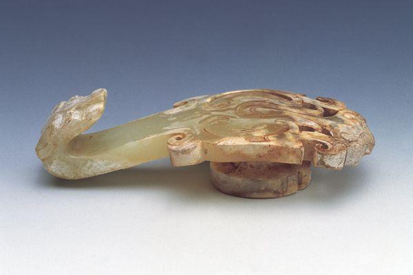 漢代.玉帶鉤 帶鉤器身加寬,採藝術鏤空法透雕為蓓蕾或鳳鳥的身軀,形制頗為優美。(圖三)