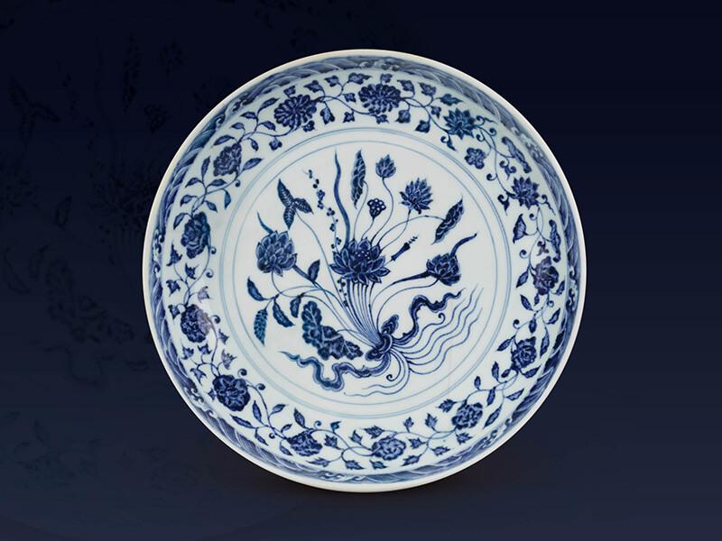 明永樂.青花盤 此器以束蓮紋為主紋,周邊搭配帶狀花卉與海水波濤紋,形成同心圓式的布局。(圖一)