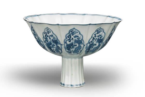 明宣德.青花高足碗 碗體做成十葵瓣造形,分別繪畫菱花形開光與雙鳳紋,風格精巧雅緻。(圖五)
