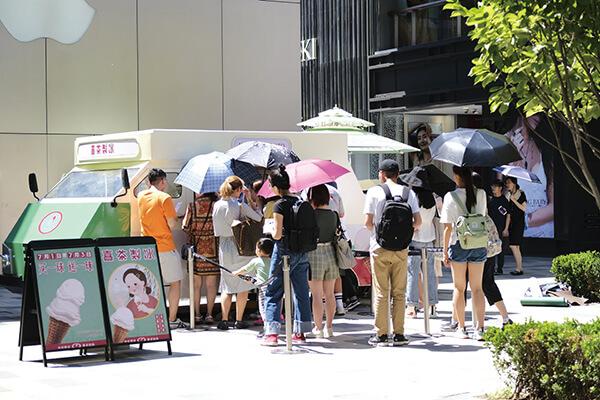 炎炎夏日,人們在喜茶製冰巴士前排隊
