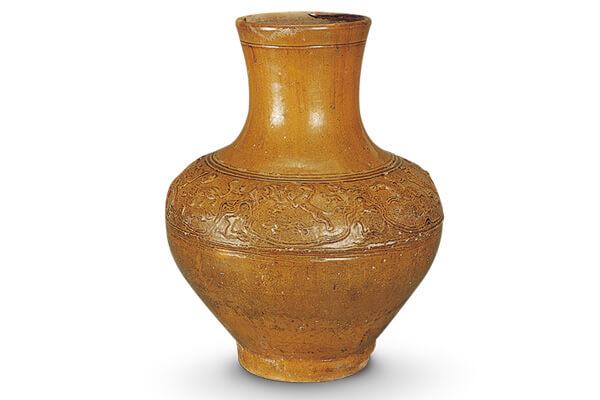 漢代.褐釉陶壺 陶壺表面模印弦紋和狩獵紋,並施以鐵為著色劑的鉛釉,燒成平滑光亮的褐色釉面。(圖四)