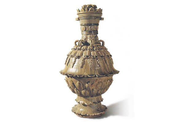 北朝.青瓷蓮花尊 器形高大,表面以高浮雕和線雕蓮花為飾,釉面玻化感強、流動性大,呈現北朝青瓷之特色。(圖五)