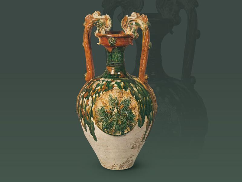 唐代.三彩貼花紋龍耳瓶 此器為盤形口、長頸、深腹、雙龍耳的形制,表面以貼花和多色釉彩裝飾,是唐代頗為流行的款式。(圖一) 圖片來源:《世界陶磁全集11隋唐》,頁51,圖34。