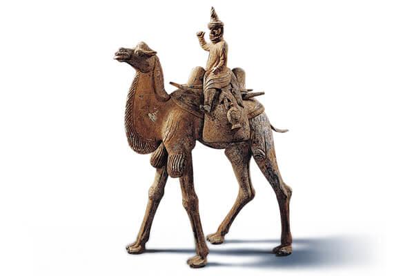 唐代.加彩人物騎駝俑 駱駝俑的體型高大,背上馱負一位頭戴高帽的胡人,呈現絲綢之路上行旅往來的風貌。(圖四)
