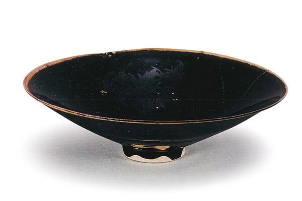 北宋.定窯黑釉金彩瑞花紋碗 胎體細白,表面高溫燒成黑釉,再彩繪金色圖案,風格富麗莊重,是比較少見的品類。(圖五) 圖片來源:《世界陶磁全集12宋》,頁25,圖17。